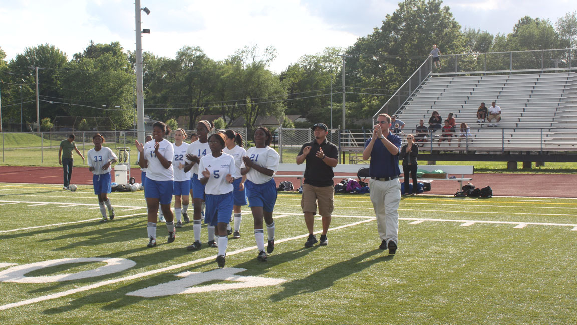 Lady Eagles run on the field, ready  for a fight, along with Head coach Luis Posada and Assistant coach Todd Barney