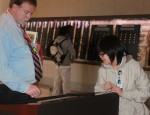 Social Studies teacher Robert Nellis examines an artifact with senior Yerym Baek at the WW! museum field trip.