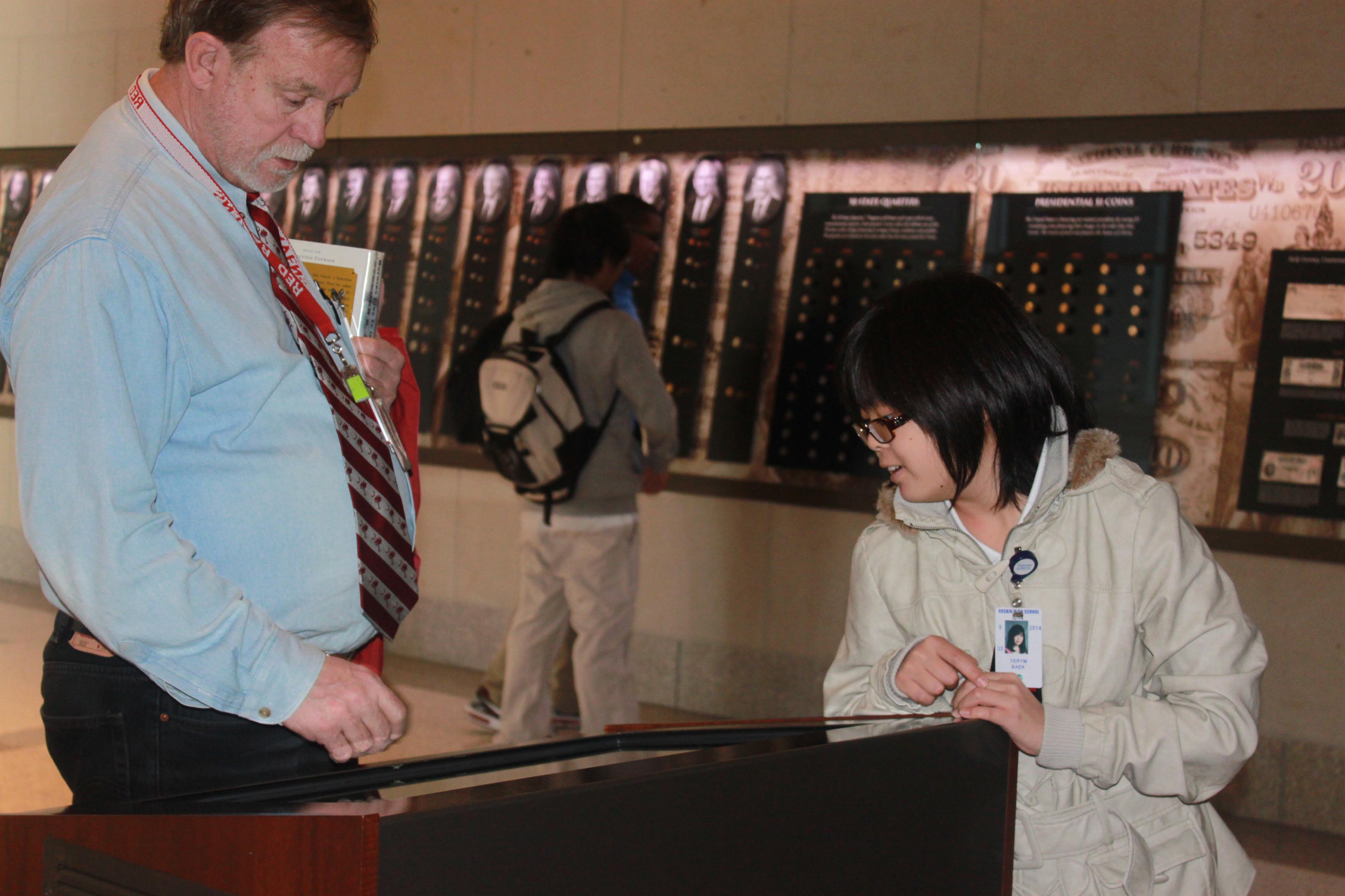 Social Studies teacher Robert Nellis examines an artifact with senior Yerym Baek at the WW! museum field trip.