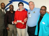 Ruskin High School junior Arik Dimond receives a $100 check for perfect attendance in March from Hickman Mills C-1 School District Superintendent Dennis Carpenter, Ruskin High School Principal Jesse Rivers (left) and Hickman Mills Educational Foundation Executive Director Charles Farris and Foundation President Cassandra Heard (right) on April 1.