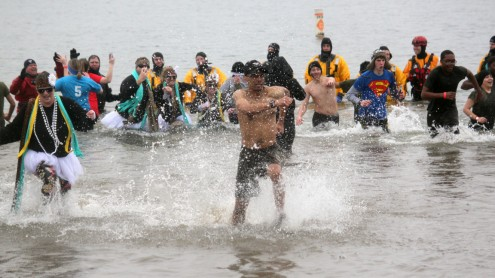 """MJROTC Instructor Colonel Ivan Glasco leads the""""Frozen Fannies"""" (left) and his Cadets (right) out of the cold waters at the Polar Plunge Saturday. The event raises money for Special Olympics. This is the second year that Glasco and his cadets have participated, and the fifth year for the """"Frozen Fannies"""" - a group of Ruskin teachers - have joined in the fun. """"I was very motivated,"""" Glasco said. """"Motivated to get out of that water AND to raise money for Special Olympics!"""" Photo by Luis Jimenez."""