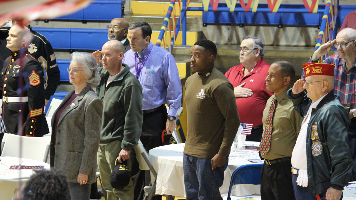 """The veterans salute the flag while the ROTC sings the National Anthem at the annual Veteran's Day celebration Nov. 11 at Ruskin High School. This is the first year Ruskin decided to do a lunch for the veterans. In previous years, Ruskin would have a breakfast to honor the veterans. At the lunch, the ROTC showed a video on WWII and also performed a traditional Marine routine. """"It was very good and Ienjoyed every single moment of it,"""" veteran Fred Krabbe said. Copy by Craig Hughes;Photo By: Luis Jimenez."""